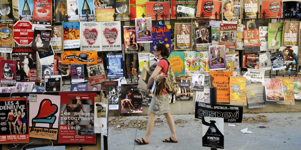 "An actress walks with posters of her theater show which is to be performed during the Avignon ""Off"" Theater Festival, two days before the opening of the 64th official Avignon festival, on July 5, 2010 near the Palais des Papes in the French southeastern city of Avignon. The festival runs from July 7 to next July 21, 2010. AFP PHOTO ANNE-CHRISTINE POUJOULAT / AFP / ANNE-CHRISTINE POUJOULAT"